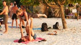 Phangan, Tailandia - 23 de febrero de 2019 Zen Beach La gente joven hace yoga del acro en la arena ejercicios del poder al aire l almacen de metraje de vídeo