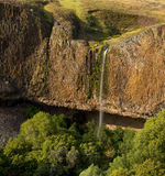 Phantom Falls in Late Afternoon. Dramatic waterfall cascades over majestic cliffs at sunset, with forest below and meadows above royalty free stock photo
