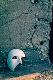 Phantom of the Opera mask. By a gritty crumbling vintage cement stone wall Stock Photos