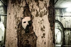 Phantom of the Opera mask. On a gritty crumbling vintage stone column Stock Images