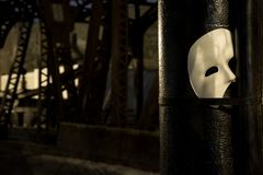 Phantom of the Opera mask. On a dark gritty retro vintage steel bridge stock photo