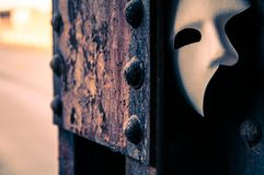 Phantom of the Opera mask. On a dark gritty retro vintage steel bridge Royalty Free Stock Image