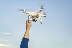 Phantom 4 pro quadcopter drone flying. CARR, CO, USA - APRIL 12, 2017: Launching DJI Phantom 4 pro quadcopter drone - operator hands and drone against sky stock photo