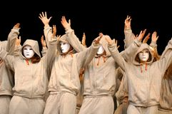 Phantoms. White-masked performers holding hands up in the air, isolated on black background Royalty Free Stock Photography