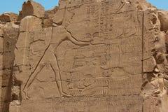 Pharao, das eine Gruppe seiner besiegten Feinde durch Seile um ihre Hälse hält, bevor sie mit einer Waffe in seiner rechten Hand  Stockfotografie