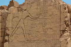 Pharaoh holding a group of his defeated enemies by ropes around their necks before killing them with a weapon in his right hand. Temple of Karnak, Luxor, Egypt stock photography