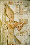 Pharaoh Ptolemy IV at Deir el Medina. Ancient Egyptian bas relief carving of Pharaoh Ptolemy IV making an offering to the gods.  Temple of Deir el Medina, Luxor Stock Photography