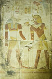 Pharaoh Seti offering to Anubis. Ancient Egyptian bas relief showing the Pharaoh Seti I making an offering to the jackal headed god Anubis. Temple to Osiris at royalty free stock photography