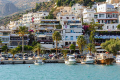 PHarbour of Aghia Galini town with parked fishing boats and beautiful houses on the rocks at Crete island. AGHIA GALINI, CRETE, GREECE - AUGUST 2015: Harbour of Stock Photo