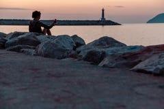 Phare au coucher du soleil Contre le contexte des montagnes photos libres de droits