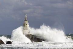 Phare au-dessus des vagues en mer orageuse à la lumière du soleil Photo stock