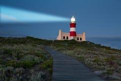 Phare avec la lumière brillante en obscurité et nuages bleu-foncé Image stock