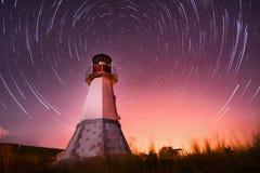 Phare avec le ciel nocturne aux traînées d'étoiles de fond Photographie stock libre de droits