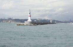 Phare blanc en mer près de la ville Photos libres de droits