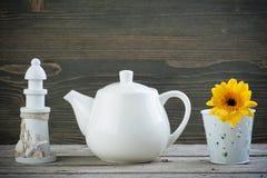 Phare décoratif, théière blanche et fleur jaune image stock