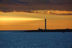 Phare dans le coucher du soleil avec le rayon de la lumière Images libres de droits