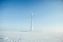 Phare dans un paysage calme et désolé d'hiver Un blanc a blanchi le phare au-dessus du ciel bleu avec des nuages Photo stock