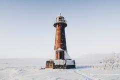 Phare dans un paysage calme et désolé d'hiver Un blanc a blanchi le phare au-dessus du ciel bleu avec des nuages Photo libre de droits