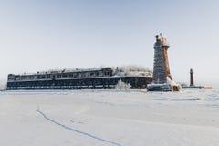 Phare dans un paysage calme et désolé d'hiver Un blanc a blanchi le phare au-dessus du ciel bleu avec des nuages Images stock