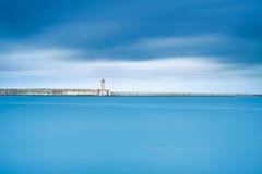 Phare de port de Livourne, brise-lames et eau molle sous le ciel nuageux Photos stock