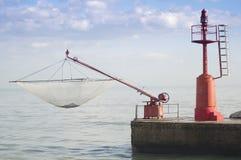 Phare et filet de pêche rouges Photo libre de droits