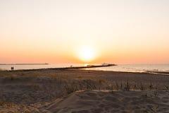 Phare pendant un de derni?re minute du coucher du soleil avec un grand soleil pr?s de l'horizon et du ciel clair photo stock