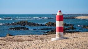 Phare rouge et blanc vibrant à la plage le jour ensoleillé au Portugal photos stock