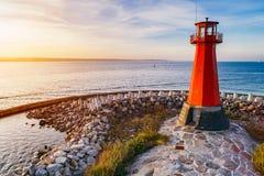 Phare rouge sur le bord de la mer rocheux photo libre de droits