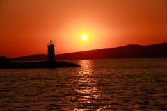 Phare silhouetté contre un coucher du soleil Images stock