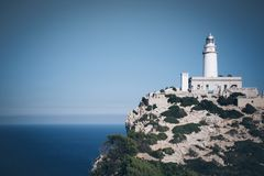 Phare sur la falaise avec le ciel bleu et l'océan Image libre de droits