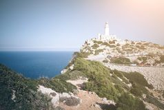 Phare sur la falaise avec le ciel bleu et l'océan Photographie stock libre de droits