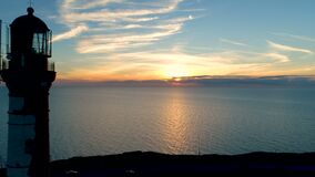 Phare sur un fond de coucher du soleil en mer Envergure du bourdon après le phare au coucher du soleil banque de vidéos