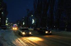 Phares de voiture en chutes de neige une nuit d'hiver dans une ville Image libre de droits