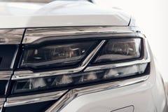 Phares en gros plan d'une voiture blanche moderne de couleur D?tail sur la lumi?re plan d'une voiture Concept moderne et cher de  photo stock