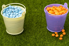 Pharmaceutical concept. Two buckets filled with orange and blue pills Stock Photography