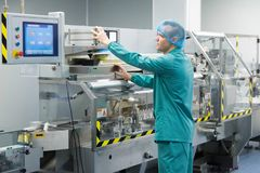 Pharmaceutical factory man worker in protective clothing operating production line in sterile environment. Pharmaceutical technician in sterile working Royalty Free Stock Image