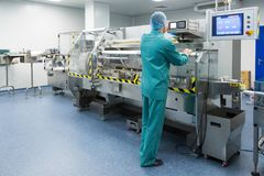Pharmaceutical factory man worker in protective clothing operating production line in sterile environment. Pharmaceutical technician in sterile working Royalty Free Stock Images