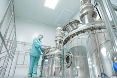 Pharmaceutical factory woman worker in protective clothing operating production line in sterile environment. Pharmaceutical technician in sterile environment at stock images
