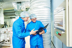 Pharmaceutical male workers in water preparation production line Stock Photos