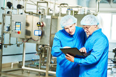 Pharmaceutical male workers in water preparation production line Royalty Free Stock Image