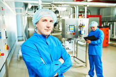 Pharmaceutical man worker operating air conditioning equipment. Two pharmaceutical technician male workers operating water preparation production line at Stock Photos
