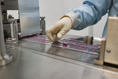 Pharmaceutical production. With bliser packing machine and human hand in gloves Royalty Free Stock Photography