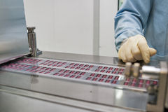 Pharmaceutical production. With bliser packing machine and human hand in gloves Royalty Free Stock Image