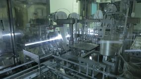 Pharmaceutical production plant. Robotic manipulator arms with containers or test tubes with blood on automated conveyor at modern pharmaceutical production stock video footage