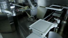 Pharmaceutical production plant. Robotic manipulator arms with containers or test tubes with blood on automated conveyor at modern pharmaceutical production stock footage