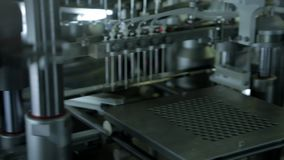 Pharmaceutical production plant. Robotic manipulator arms with containers or test tubes with blood on automated conveyor at modern pharmaceutical production stock video