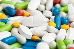 Pharmaceutical products. Close-up of pile of drugs, many different pills and tablets of different color blue, red, yellow Stock Photo