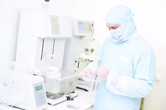 Pharmaceutical researcher with friability and abrasion tester in laboratory. Pharmaceutical scientific male researcher in protective uniform working with stock images