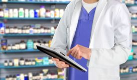 Pharmaceutical staff at drugstore with medicine in background Royalty Free Stock Photography