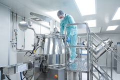 Pharmaceutical factory man worker in protective clothing operate production line in sterile working conditions. Pharmaceutical technician in sterile environment Stock Photos